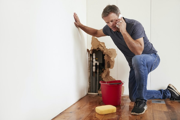 middle aged man calling an emergency plumber due to his broken pipes in the wall